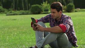 Varón que se sienta en la hierba usando una tableta almacen de metraje de vídeo