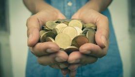 Varón que sostiene monedas de oro del dinero en su mano para financiero imagen de archivo libre de regalías