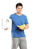 Varón que sostiene una escala del peso y plátanos Imagen de archivo libre de regalías