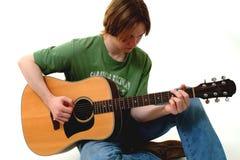 Varón que toca la guitarra acústica Imagenes de archivo