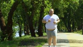 Varón regordete con el vientre grande que corre en parque, la motivación y la forma de vida sana metrajes