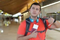 Varón relajado que comprueba el tiempo en el aeropuerto Imagen de archivo libre de regalías