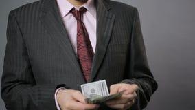 Varón rico en el traje que cuenta el dinero y que da extremidad de 100 dólares alguien, ascendente cercano almacen de video