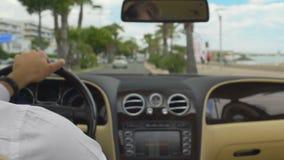 Varón rico que conduce el camino costoso del coche abajo cerca de la orilla del mar, vacaciones de lujo almacen de metraje de vídeo