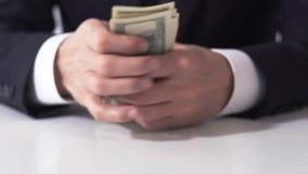 Varón rico que cuenta los billetes de banco del dólar, manos del hombre de negocios que estiman renta metrajes
