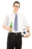 Varón sonriente con el lazo que sostiene una botella y una bola de cerveza Imagenes de archivo