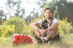 Varón sonriente de la tarjeta del día de San Valentín con el manojo de rosas que se sientan en hierba Fotos de archivo libres de regalías