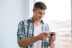 Varón sonriente hermoso usando smartphone Imágenes de archivo libres de regalías