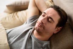 Varón tranquilo que tiene siesta en casa Fotografía de archivo libre de regalías