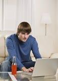 Varón trigueno usando la computadora portátil Foto de archivo libre de regalías