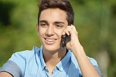Varón usando el teléfono celular y feliz Imagen de archivo