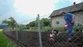 Varón usando la máquina moderna para arar sobre la cerca metrajes