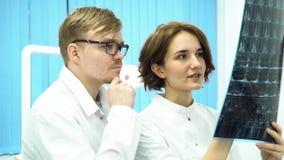Varón y doctores de sexo femenino que discuten exploraciones de cerebro en el hospital Hombre que pone en los vidrios y la mujer  metrajes