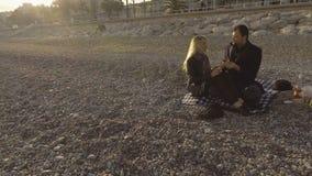 Varón y femenino teniendo comida campestre en la playa en Niza, muchacha de alimentación del individuo con la fresa metrajes