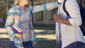 Varón y femenino teniendo conversación agradable, abrazo feliz de los amigos de la universidad almacen de metraje de vídeo