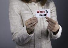 Var att investera? Affärskvinna som rymmer ett kort med en meddelandetex Royaltyfria Foton