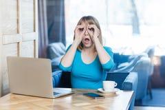 Var dig? Ståenden av den förvånade unga affärskvinnan i blå blus sitter i kafé och rymmer hennes händer nära ögon som framställni fotografering för bildbyråer