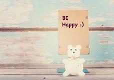 Var lycklig skrev den pappers- ställningen och den gulliga björnen på grungeblått träb Arkivfoto