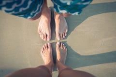 Var?n y pies femeninos en la arena foto de archivo libre de regalías