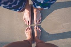 Var?n y pies femeninos en la arena fotografía de archivo libre de regalías