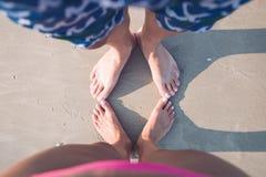 Var?n y pies femeninos en la arena imagen de archivo