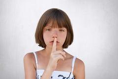 Var tyst, hyssja! Den förtjusande lilla ungen som visar det tysta tecknet som frågar att vara ljudlös som hennes lilla syster, so arkivbild