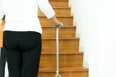 Vara asiática idosa da terra arrendada da mulher ao andar acima da escada em casa, fim acima fotos de stock royalty free