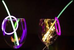 Vara azul e verde do fulgor em um vidro de vinho com celebração do ano novo com aginst claro colorido do relection o partido es foto de stock