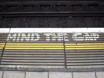 Vara besvärad mellanrummet, en visuell varning på en plattform av stationen för den London rörinvallningen arkivfoton