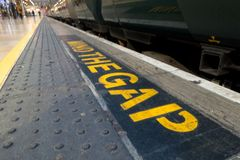 Vara besvärad mellanrummet målas längs kanten av plattformen på en järnvägsstation i London Royaltyfri Fotografi