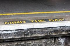 Vara besvärad mellanrumsvarningen som målas på den järnväg plattformen arkivbild