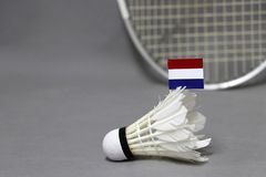 A vara da bandeira de Mini Netherlands na peteca branca no fundo cinzento e focaliza para fora a raquete de badminton fotografia de stock royalty free