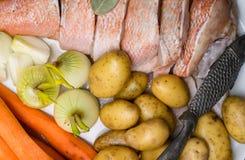 Vara de mar cru, com especiarias dos peixes, cenoura, batatas, pimenta, cebola, folha de louro, aipo no fundo escuro Alimento sau Fotos de Stock