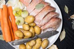 Vara de mar cru, com especiarias dos peixes, cenoura, batatas, pimenta, cebola, folha de louro, aipo no fundo escuro Alimento sau Fotografia de Stock Royalty Free