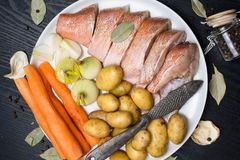 Vara de mar cru, com especiarias dos peixes, cenoura, batatas, pimenta, cebola, folha de louro, aipo no fundo escuro Alimento sau Foto de Stock