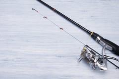 Vara de pesca com o carretel no canto de um claro - fundo cinzento da tabela, um lugar para sua inscrição imagem de stock