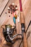 Vara de pesca com um punho cortical e um carretel de pesca Uma variedade de flutuadores Isca de pesca dos boilies e das pelotas imagens de stock
