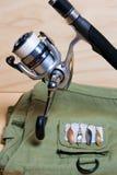 Vara de pesca e carretel com veste da pesca Imagens de Stock Royalty Free