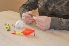 Vara de pesca e spinnings na composição com os acessórios para pescar no fundo na tabela Fotos de Stock Royalty Free
