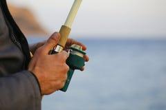 A vara de pesca na mão humana Imagens de Stock