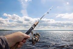 Vara de pesca na mão no fundo de um rio largo em um s fotografia de stock