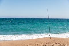 Vara de pesca na praia no dia ensolarado imagem de stock