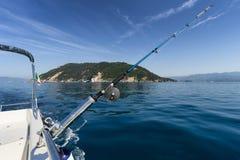 Vara de pesca no barco com a ilha no fundo Fotografia de Stock