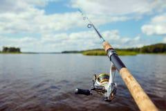 Vara de pesca no fundo de uma ilhota borrada da grama verde Fotografia de Stock