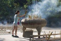 Vara do incenso da inserção da jovem mulher no incensário, monastério do Po Lin, Imagem de Stock Royalty Free