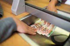 Vara kontorist att ge kontanta pengar till kunden på bankkontoret royaltyfri bild