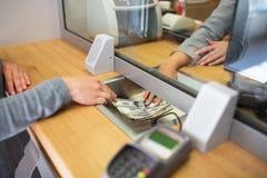 Vara kontorist att ge kontanta pengar till kunden på bankkontoret royaltyfria bilder
