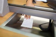 Vara kontorist att ge kvittot på banken eller valutaexchangeren royaltyfria bilder