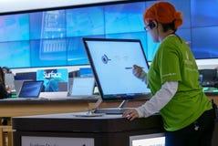 Vara kontorist målning på den nya datoren på det Microsoft lagret Arkivfoton