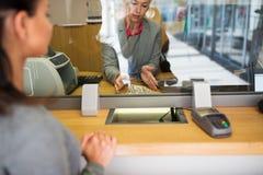 Vara kontorist med kontanta pengar och kunden på bankkontoret royaltyfria foton